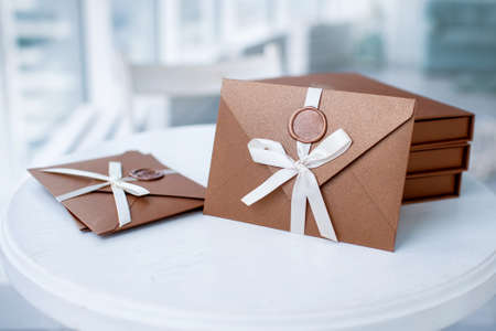 Photo pour Gift Certificate, gift voucher or discount. close-up photo of bronze invitation envelope with a ribbon and wax seal, a gift certificate, a card, a wedding invitation card - image libre de droit