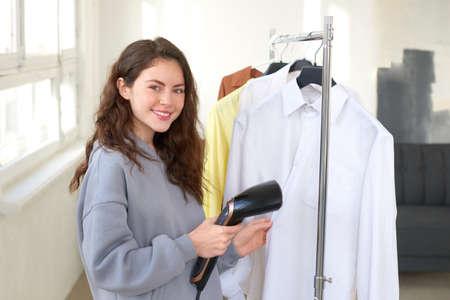 Photo pour young woman steaming elegant shirt with electric steamer - image libre de droit