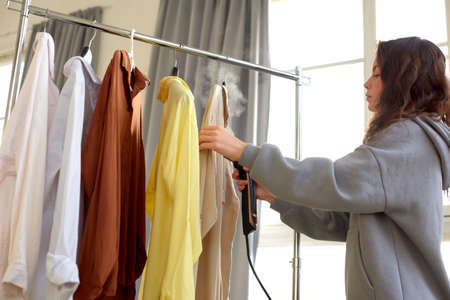 Photo pour Girl steams clothes on hanger. Woman with steamer cleaning clothes in dry-cleaning salon - image libre de droit