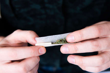 Photo pour Drugs narcotic concept. Close up of addict lighting up marijuana joint with lighter. Close up . Drug use. Man rolling a marijuana joint. Man preparing and rolling marijuana cannabis joint. - image libre de droit
