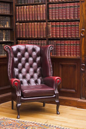Photo pour Traditional Chesterfield chair in classical library room - image libre de droit