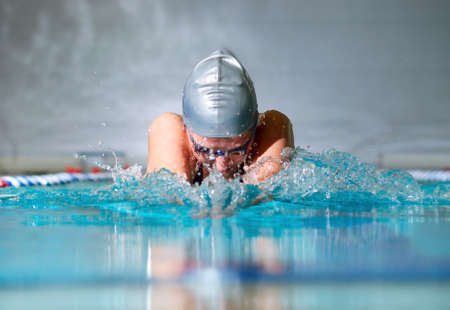 Photo pour woman swims using the breaststroke in indoor pool  - image libre de droit