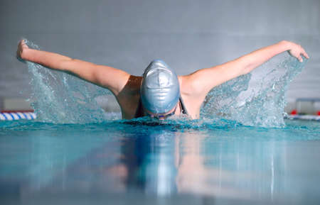 Photo pour woman swims using the butterfly stroke in indoor pool - image libre de droit
