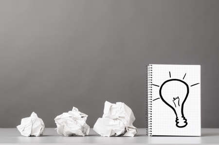creative process  crumpled wads and notebook with bulb picture