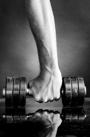 Foto de male hand is holding metal barbell on dark gray background - Imagen libre de derechos