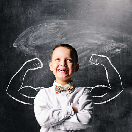 Photo for school boy is standing with strong hands on blackboard behind him - Royalty Free Image