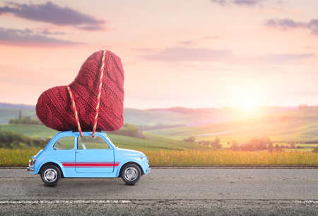 Foto de Blue retro toy car delivering heart for Valentine's day against blurred rural Tuscany sunset landscape - Imagen libre de derechos