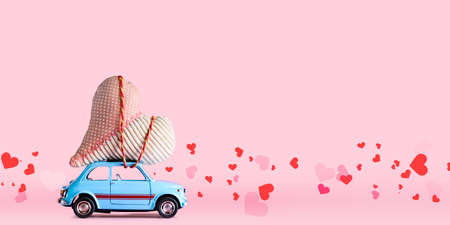 Foto de Blue retro toy car delivering craft heart for Valentines day on pink background with confetti - Imagen libre de derechos