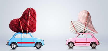 Foto de Couple of retro toy cars delivering craft hearts for Valentines day on gray background - Imagen libre de derechos