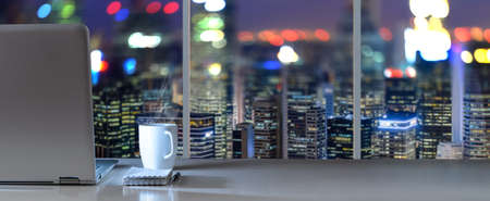 Photo pour Laptop on table in office with panoramic night view of modern downtown skyscrapers at business district - image libre de droit