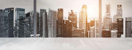 Photo for Desk with blurred panoramic view of Singapore downtown and skyline at sunset in office window. - Royalty Free Image