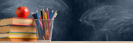 Photo pour Back to School. Accessories, books and fresh apple against chalkboard - image libre de droit