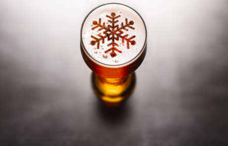 Photo for Christmas or New Year beer concept. Snow symbol on beer glass foam on black table, view from above - Royalty Free Image