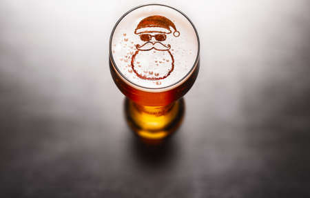 Photo for Christmas or New Year beer concept. Star symbol on beer glass foam on black table, view from above - Royalty Free Image