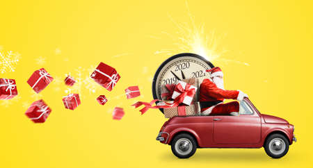 Photo pour Christmas countdown arriving. Santa Claus on snowy toy car delivering New Year gifts and clock at yellow background - image libre de droit