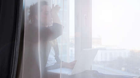 Photo pour Bored yawning woman working on laptop from home due to coronavirus self isolation. Sitting on window sill. Authentic home workplace. Coronavirus outbreak 2020. - image libre de droit
