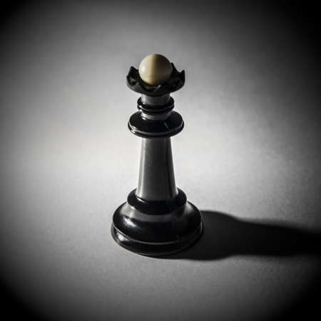 black chess queen stands on the white background, tight shadow, radial gradient
