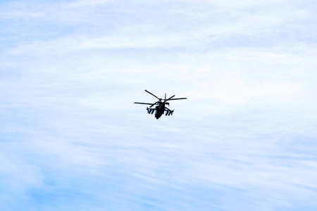 Photo for Russian military combat attack helicopter K-52 Alligator flies against the blue sky and clouds - Royalty Free Image