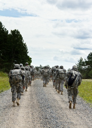 Soldiers are marching on a gravel road
