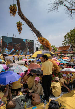 thai people watch a video during the coronation of His Majesty King Maha Vajiralongkorn Bodindradebayavarangkun or King Rama X, Bangkok, Thailand