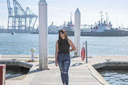 beautiful mexican girl walk on pier with boats in the background