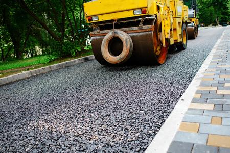 Carrying out repair works: asphalt roller stacking and pressing hot lay of asphalt. Machine repairing road.