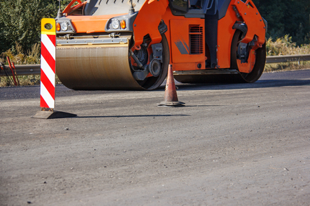 Photo pour Carrying out repair works: asphalt roller stacking and pressing hot lay of asphalt. Machine repairing road. - image libre de droit