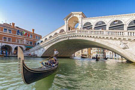 Foto de Gondolier rowing a tourist family in gondola in front of the Rialto Bridge in Venice, Italy. - Imagen libre de derechos
