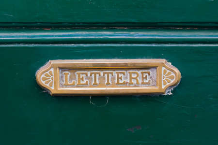 Old brass letterbox on a green door