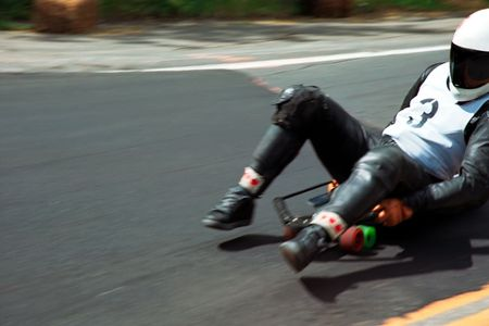 racing downhill with speed skateboard or toboggan