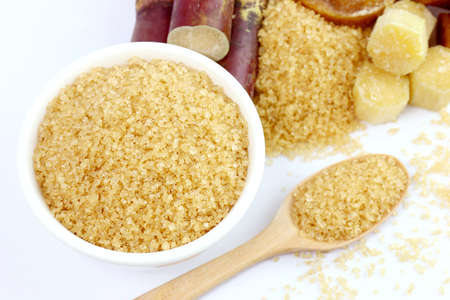 sugarcane sugar, granulated sugar brown in a white cup, granulated sugar yellow on spoon wooden over white background