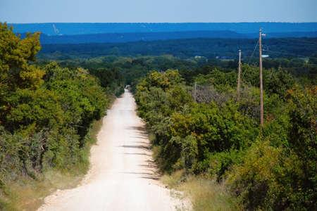 Photo pour Rural dirt road to horizon in hills of Texas landscape. - image libre de droit