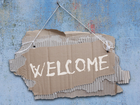 Cardboard sign with message WELCOME . Ripped corrugated paper on a rope hanging on a nail on a cracked wall and  with handwritten inscription WELCOME.