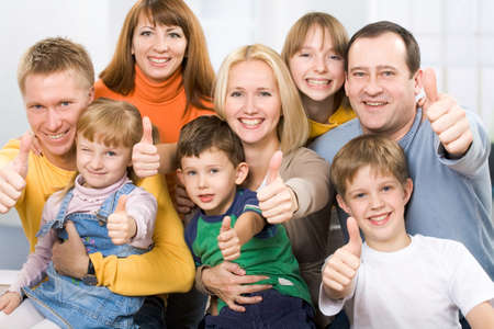 A portrait of a large prosperous family with their thumbs up