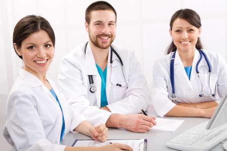 Photo pour Smiling medical doctors on a workplace - image libre de droit