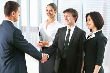 Business people shaking hands, finishing up a meeting at office