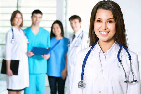 Portrait of young female doctor standing in frount of his team and smiling