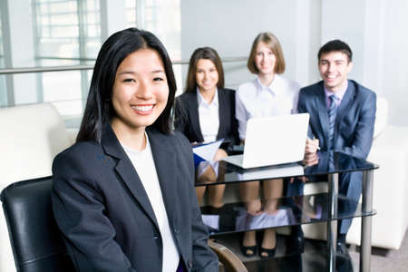Portrait of a smiling young asian business woman in a meeting