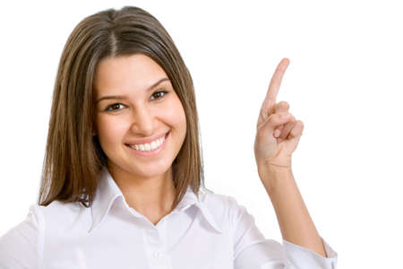 Closeup portrait of a happy young business woman pointing at something interesting against white backgroundの写真素材
