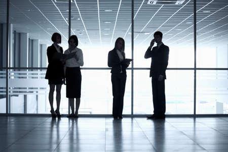 Photo pour Business people silhouettes in a modern office - image libre de droit