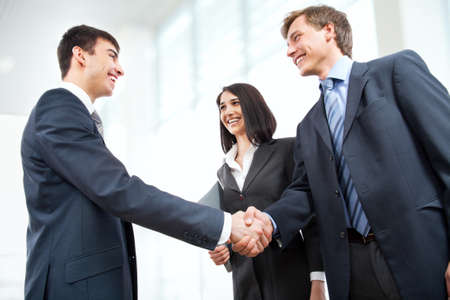 Business people shaking hands in modern officeの写真素材