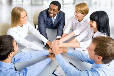 Photo pour View from above of business team making pile of hands on working place - image libre de droit