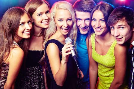 Photo pour Young people singing into microphone at party - image libre de droit