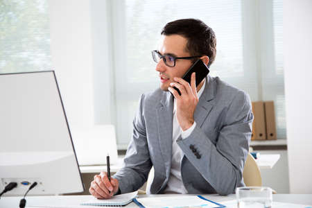 Foto de Young handsome businessmantalking on the phone in an office - Imagen libre de derechos