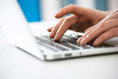 Foto de Close-up of hands of businesswoman typing on a laptop. View through blinds - Imagen libre de derechos