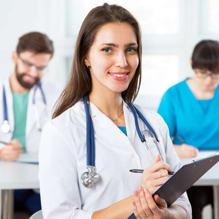 Photo pour Portrait of a young female doctor in a clinic with colleagues on the background - image libre de droit