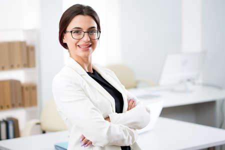 Photo pour Portrait of a smiling young attractive business woman in an office - image libre de droit