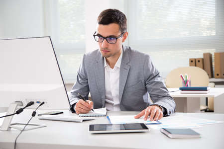 Photo pour Serious businessman working with computer in an office - image libre de droit