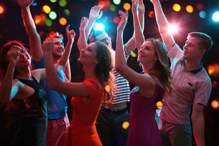 Photo pour Group of happy young people having fun dancing at party. - image libre de droit