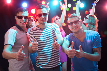 Photo pour Happy young friends showing OK sign in the night club - image libre de droit